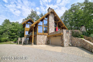 IMPRESSIVE SCANDINAVIAN FULL SCRIBE LOG HOME built with massive round logs~is fully handcrafted & energy efficient all with deeded Lake Michigan Access. Perfectly situated on top of a dune to enjoy the peaceful serenity, incredible sunsets & breathtaking views of Lake Michigan. This special one-of-a kind home features vaulted ceilings, walls of glass throughout, bringing the outside in to the 3100 sf of comfortable living space. Ideal for entertaining is the spacious 2 story great room w/massive floor to ceiling stone fireplace & dining room. Stunning kitchen boasts new stainless-steel appliances & granite countertops & cozy sun room has beautiful wooded views. Upper level features office/guest room & Luxury Master Suite w/expansive windows, spacious bath w/stone surround soaking tub & granite topped vanity w/double sinks Two Generous bedrooms & full bath on the lower level. Outdoor viewing deck w/stone fireplace. Natural landscaping. Beach access in Sheldon Dunes Assoc is just minutes away. Call for your private showing.