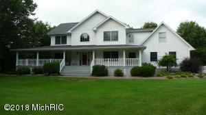 Front of home with grand wrap around porch.