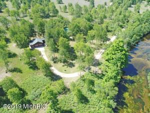 You will fall in love with the privacy, the endless wildlife and the quiet, peaceful surroundings at your new Betsie River home. With over125 acres and over 1700 feet of private (no bluff) Betsie River frontage, you can literally kayak or canoe right outside your door, hunt forhours, snowmobile (trail head is located at the end of the driveway), ride your ATV and much more! The land is perfect for everyone wholoves nature, wildlife and outdoor sports and recreation. The wildlife enjoys calling this property home also - there are endless salmonswimming in the river, beautiful bald eagles soaring above, deer and turkey roaming about the land and most of all peaceful quiet! Theland is a mixture of cherry, pines and some oak. The north property line connects you to thousands of acres