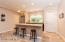 Lower level kitchenette / bar area features granite , bar seating area and refrigerator