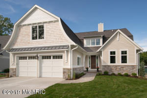 Lake Cottage with gambrel roof design accented with shake and Hardie siding