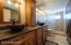 Elegant master bath features ceramic floors, titled shower, quartz counter tops, hickory vanity and copper sink basins.