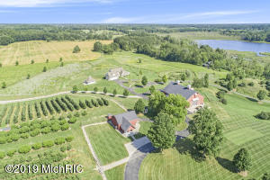 Welcome to ''Honey Creek Farm!'' An amazing 100+ acre property offering a custom-built manor-style house, multiple outbuildings, a fruit tree orchard, tillable land, meadows, trails, and wooded acreage with Egypt Creek meandering through it. An opportunity of this magnitude doesn't present it itself often in Ada Township. This is a must-see property with endless options for a large farm estate or future redevelopment! From the wooded and rolling hills of the land to the custom designed home, everything about this property exudes quality. The almost 7,700 square foot house, designed by architect Chuck Posthumus, offers custom features such as an open floor plan; casual and formal living spaces; a gourmet kitchen with professional appliances, walk-in pantry, and huge island; back hall space for a butler's pantry, planning area, pet room, and laundry; giant master suite with long views over the land, his/hers closets, custom built-ins, and a spa-like bath; screened porch with views of the meadows; two more bedrooms; a sitting area and office plus plenty of lower level space to create an entertainment mecca. Three outbuildings on the property, also all custom and designed by architect Chuck Posthumus, consist of a 7,000 SF residential-quality barn that features a full kitchen, eating area, full bath, office, space for a bunk room, glass overhead doors plus lots of finished open storage for equipment; a 1,900+ SF roadside farm market with market stand, giant 36° F cooler, storage space, and workshop; and a 780 SF heated kennel with hot and cold water. Please see media for extensive detail!