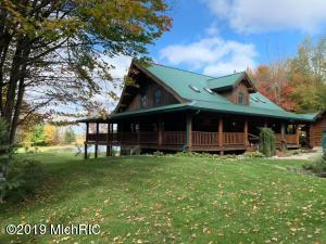 Pure Michigan paradise! You'll never want to leave this property once you visit! Winding down the driveway through the woods you may have a few turkey or deer welcome you! This custom log home on 110 acres has much to offer the outdoor enthusiast. Log homes come in many shapes, sizes, and quality level, and this Snowy Range is of top quality and craftsmanship. The home itself offers 4 bedrooms, 3.5 baths, and a finished walkout basement with a second full kitchen, dining, and living area. Main floor laundry, master suite, and guest bathroom. Loft with an office area, two bedrooms and another full bathroom. Walkout basement has an oversized bedroom and full bathroom. The main floor and walkout overlook your pond and garden area, and the home has a complete wrap around deck to enjoy the view from any angle.  Oversized pole barn and two car garage.  The 110 acres is a complete setup to walk on and hunt.  Trails, food plots, blinds, woods, tillable (tiled) - this property has been strategically managed very well.