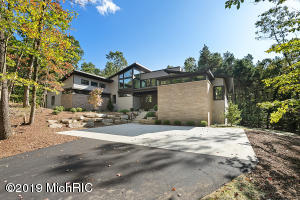 Just minutes from downtown Ada, on a private cul-de-sac perfectly cut into 2.46 acres of wooded land sits this stunning contemporary architectural masterpiece designed by AMDG Architects and constructed by the esteemed Bruce Heys Builders. Natural light floods this 2019 Parade home throughout the entire expanse, bringing beautiful natural surrounding views indoors. Walk through the double door entrance into the expansive living space complete with a custom concrete fireplace. The gourmet kitchen features a walk in pantry and large island with quartz countertops, dining room with tray ceiling and private conversation area past the fireplace. Main level master suite with a walk-in closet and the stunning bathroom featuring a soaking tub and exquisite shower. The powder bathroom, main level laundry and locker area and three stall garage complete the first floor. Upstairs loft with floor to ceiling windows is a perfect get-away space for TV or lounging. There are four bedrooms and two bathrooms in the incredible second floor living space. The walk-out lower level has in-floor radiant heat and the builder is finishing the ample living space, kitchenette, guest room and full bathroom per buyers finish selections. Call for a private tour today!