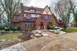 """This EGR all-brick, French Tudor-style residence, with circular drive, has the charm of another era and the conveniences for today's modern living. With more than 4500 square feet of finished living space, it includes 6 bedrooms, 3 full and 2 half bathrooms. Substantial crown moldings, bay windows, gleaming hardwoods, graciously proportioned rooms, multiple fireplaces and a spacious kitchen are simply a few of the appealing features. Adjacent to the living room is a library with impressive cabinetry. The property is 3/4's of an acre and splits are available with zoning approval. The extensive gardens, patio, gazebo, in-ground pool and expansive backyard are perfect for entertaining, family gatherings or a peaceful retreat. The lower level has new paint, carpet and a second kitchen. It's a great opportunity to have an exceptional home, a beautiful setting and walking distance to everything that's """"cool"""" about East Grand Rapids."""