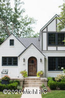 All the character of its 1923 roots; every modern amenity and mechanical system found in high end new construction with a complete surprise described later. This brick English cottage style home underwent a full gut interior and exterior remodel and addition in 2016. The home was designed and is owned by nationally known, award-winning designer, Jean Stoffer. Everydetail, every finish, every design element was carefully and artfully crafted using uniquely beautiful high end, customized materials installed by skilled craftsmen. This truly is an unusual home for today, as it has all the best and most enjoyable aspects of an old home, yet can be experienced with all the confidence, convenience, and comfort of a new home.  Its location in East Grand Rapids, Michigan is ideal. The main home's living space has an international award winning kitchen designed with SubZero and Wolf appliances and other custom made, high end materials. It is open to a dining area (with connected Butler's Pantry) and family room with fireplace. Doors from the dining area to the outdoor terrace create a wonderful indoor/outdoor experience. Reclaimed wood floors, milled on site give the home a cozy, collected feel. New roof, windows, and insulation, along with new energy efficient, multi-zoned heating and cooling systems make the home quiet, warm in the winter, cool in the summer. The first floor master suite is appointed with exquisite bathroom, his and her closets, vaulted ceiling and doors to a covered terrace. The laundry is steps away. The second floor is guest ready with two handsome bedrooms, one with a lake view, one bathroom with vaulted ceiling, with reading nook at the top of the stairs. The unfinished, dry basement is great for storage, a play place for kids, or ready for finishing. The surprise of this property is the full guest house with separate entrance above the three car plus attached garage. Two bedrooms, each with a walk-in closet large enough for a crib, designer bathroom, 