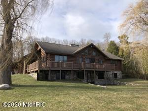 Quality-built log home with 100 ft of private frontage on PORTAGE LAKE, which leads out to LAKE MICHIGAN. If you're looking for privacy, this is it. No neighbor on one side (a rare find for waterfront), and views of the Portage Point Inn. Four large bedrooms, three full bathrooms, spacious-open feel throughout, an attached two-car garage and two beautiful, stone, natural gas fireplaces; one on each floor. Central Air is ready for your summer relaxation. And the enormous deck is ideal for watching the wildlife and the stars. Lots of room for parking for all of your friends and family!! You must see this one in person. And if you've seen it once, you should take another look. (Ideally located between Arcadia Bluffs, Crystal Mountain and Manistee's Meijer.)  80-ft wooden dock is included!