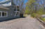 Driveway to garage and wooded lot with walking trails in the back.
