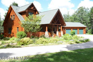 This custom log home is located on 10 wooded acres in Grand Traverse County. The home is constructed of northern white cedar with insulated 2x6 exterior walls. The property is only 15 minutes from Traverse City which offers some of Michigan's finest restaurants, four seasons of recreational activities, theaters, and quaint shopping locations. This 5375 square foot home offers many amenities including; six bedrooms, 3 1/2 bathrooms, a large covered front porch and a fabulous 3-seasons room. Additional features include a beautiful kitchen with custom cherry cabinets and granite countertops, large center island (maple top) with prep sink and seating for three and a planning desk. There is a large laundry/mud room and walk-in pantry located just off the kitchen