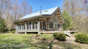 Enjoy the Kalamazoo Riverfront at your year round retreat on 20 Acres in Saugatuck Township. Soaring to 22 feet high the log beams create open living spaces with large loft for entertaining. Nature's beauty surrounds the homestead and can be enjoyed from the large sun room, huge deck and covered front porch. 1st Floor Master Suite includes custom touches with claw foot tub, oversized walk-in shower plus dressing room/closet with laundry. Artistry and creative touches in cabinetry, hardware, and finishes. Lower Level high ceilings, daylight windows, full bath provides customized living options. Space could be 2 more bedrooms, home office or media room. Large custom Log Home with 2 out buildings. Add a pole barn for toys. Close to the Public Boat Launch, Douglas, Saugatuck and Lake Michigan!