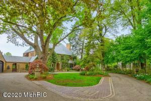 One of the oldest, grandest homes on Lake Macatawa, this classic all brick 4500 sqft Tudor has been masterfully remodeled boasting 165' of prime frontage with views beyond compare.  Main floor greets you with a slate and granite entry, marble, and hardwood throughout the home and features a lakeside sunroom, formal dining, formal living room, sun porch, 1/2 bath, and newer kitchen; new baths, kitchen, windows, New Fujitsu AC units throughout, doors, blinds, paint, etc, etc. Lower level has been finished with 2nd kitchen and office, as well as a new exercise room/ 5th bedroom, a spa/massage room, and full bath.  Laundry with sets of both TROMM and BOSCH washers/dryers with laundry chute from above.   All new landscaping with Bluestone patio surrounds the new pool dressed with Arborvitae.