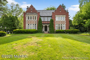 This English Tudor is a grand property in a prime East Grand Rapids neighborhood and is within walking distance to the finest school system, shops, and restaurants. Completed in 1930 and designed by Benjamin and McLaughlin architect; the meticulously restored and maintained interior of the home provides grand entertaining areas and comfortable living spaces appointed with tall, leaded glass windows, exquisite hand carved woodwork, wonderful moldings, custom inlayed floors of wood and marble, lovely wainscoting, gorgeous arched doors throughout, and a beautiful 14 carat gold Swarovski crystal chandelier. Exterior detailing is impressive made of red brick and limestone with ornamental carved oak trim.  It includes a new boiler system, hot water heater 75 gallon, appliances; Wolf Range, Viking dishwasher, Thermador wall ovens, Liehberr Refridgerator, wet bar with crystal sink, refinished heart of pine floors, heated garage, new landscaping, walkways, and blue-stone patio. New granite wet bar in basement with wood burning fireplace. Interior design pertinent to the current published photos are compliments from the previous owner EGR resident and designer Mary Rossi. Call to inquire on this beautiful property!