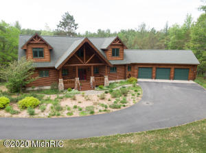 This custom log home is located on 10 wooded acres in Grand Traverse County. The home is constructed of northern white cedar with insulated 2x6 exterior walls. The property is only 15 minutes from Traverse City which offers some of Michigan's finest restaurants, four seasons of recreational activities, theaters, and quaint shopping locations. This 5375 square foot home offers many amenities including; six bedrooms, 3 1/2 bathrooms, a large covered front porch and a fabulous 3-seasons room. Additional features include a beautiful kitchen with custom cherry cabinets and granite countertops, large center island (maple top) with prep sink and seating for three and a planning desk. There is a large laundry/mud room and walk-in pantry located just off the kitchen The dining area easily accommodates seating for 8 to 12. The great room is stunning with soaring 25' tongue and groove ceiling and a stone fireplace. A large main level master suite with access to deck offers a master bath complete with a custom cherry vanity and double sinks, granite counter, 5' jetted tub and separate shower, tile floor with radiant heat and walk-in closet. Upper level features loft area, three bedrooms and full bath. The lower walkout level features family room with Vermont Castings wood burning stove, play/game room, two bedrooms, bath and mechanical room. The property is on a quiet, private road adjacent to 1,000's of acres of state forest, close to Vasa Trail and the Sand Lakes Quiet Area which offer trails for cross-country skiers, runners, hikers, mountain bikers, walkers, and naturalists to enjoy. The quaint Village of Elk Rapids is nearby which offers award-winning schools (only three miles to the elementary), a marina, restaurants, shops, theater, and great beaches. The Elk Lake boat launch, with access to the Chain of Lakes, is only 10 minutes from the property. Call today to schedule a private showing for the opportunity to fall in love with your forever home!