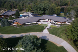 This true masterpiece, situated near Lake Michigan, sits on 40 acres, with 2 acre pond and outdoor kitchen, grill with spacious patio for entertaining surrounding an in-ground pool. The car lover's dream,12,000 SF temperature controlled building provides luxurious storage for toys and trophies, or opportunity for additional guest amenities. The 10,000+ SF home was designed by Steenwyk Architects, is your modern escape, boasting incomparable details throughout, including generously sized kitchen, theater room, workout room, and lower level bar for entertaining The master suite is an exclusive getaway with his and her walk-in closets and fireplace. Providing a unique detail to this truly one-of-a-kind home. Custom features abound in this lifestyle piece impossible to duplicate.