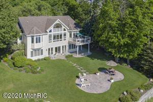Located about 1 mile north of the Holland State Park & Pier, this exceptional newer 3 bed, 3.5 bath Lake Michigan home has 75' of sandy beach frontage with some of the best beach on Lake Michigan today.  You can enjoy the panoramic views of the lake and beach from the home's Trex deck with glass balusters. Estate-like grounds & beautiful landscaping.  You can see the Holland pier and Big Red Lighthouse from the home. This custom-built home (2009) was built by Tervoort Builders w/ quality materials & craftsmanship. Great eagle eye views from most rooms in the house. The home has 2.5 stall garage, 2-zone heating, steel I-beam support, 2x6 construction, Andersen windows with clean coat and UV glazing on lake side.  Private frontage   & posts marking lot lines by beach are visible to north Main floor living includes master bedroom and bath with his and her walk-in closets, laundry, living room with gas fireplace and vaulted 2-story ceilings, formal dining room, dinette and kitchen areas, office/den that could be a 4th bedroom, a powder room/half bath, an extra deep 2.5 stall garage with hot and cold water, and a large lakeside deck. The walkout lower level has more of a cottage-style with a kitchenette, lots of natural light, exercise room (could be 5th bedroom), a family room (with a 13' wall unit), 2 bedrooms, 2 full baths ... one for when you come in off beach, a very large storage area/mechanical room, and a large outdoor patio. The lot is beautifully landscaped and provides much privacy.  Underground sprinkling, Hunter Douglas blinds throughout, copper pipes for plumbing, beautiful custom cabinetry throughout, under counter lighting, electric stove top with oven upstairs and downstairs, a built-in desk, a walk-in closet in the lower level. City water and sewer. High speed internet and cable available. Owners have 2 sets of blueprints of the home which was architecturally designed. Owners are members of the Huizenga Shores Association and use those beach stairs next door to access the owners own private beach. Seller will put together list of several items that could be bought with the home.  A seawall from 1986 exists that hasn't been needed but is there for assurance if lake levels would ever rise more than their current record highs.  $15,000 estimate to take out walls in formal dining to kitchen/Living.  And $50,000 to $75,000 to re-do formal dining area to open up to kitchen and living more.  Sound insulation in master suite for peaceful night sleep in storms or when company is still up.  Home is situated nicely about 300' back from waters' edge for peace of mind with erosion.