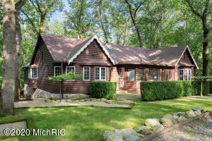 Just a three minute walk to Lake Michigan at Stop 41! Outstanding Village of Michiana log style home on a huge double lot. 5 bedrooms, 4 full baths. Unwind in the comfortable living room which boasts a vaulted ceiling with wood beams, exceptional stone fireplace, and bay window seat. The  quality-built addition to the original home offers updated kitchen and dining for family gatherings, primary bedroom suite, wonderful guest rooms and walkout lower level that includes a large unfinished recreation room.  This home is Immaculately maintained with numerous improvements. The homesite provides a substantial feeling of privacy. There is plenty of parking plus room to add a garage.  The Village of Michiana is a charming and well-run golf cart friendly community.