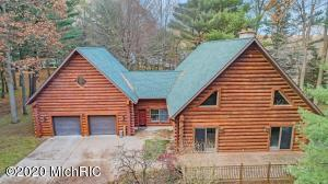 Rare find in Spring Lake so close to town & very private. Real log home on nearly 3 acres. The current owners have updated just about everything inside & out since purchasing in 2007. All 4 bathrooms were gutted & finished w/ a modern design. Aside from the wood floors, every inch of flooring has been updated. Kitchen features new granite counters, stainless steel appliances, & new lighting. Living area is bountiful, w/ 5 different living spaces throughout. Sellers invested heavily into chinking all of the joints on the logs, staining & water proofing every exterior log, & adding a new roof & gutters. There isn't a single power pole on the property, as lines were run underground. City sewer & water were run over 2 acres to the home. Butts up to the bike path for easy access all over town!