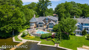 "Exquisitely crafted, coastal inspired, Lake Macatawa masterpiece. Built on a quiet bay amongst the woods, in one of Holland's premier lakefront communities, this custom home will amaze you with nearly 10,000 luxurious square feet, and only the finest high-end finishes. 6 bedrooms, complete with 2 suites, 5 full and 2 half bathrooms, along with a laundry room on 3 floors, this home is built for maximum comfort and livability. The master bedroom, with connected home office has his and hers closets, lake views, and relaxing shower with wall jets. The gorgeous exterior and grounds are highlighted by the brick driveway with complete snowmelt system, steel seawall, lakeside pool and spa, and outdoor kitchen. A boaters dream, the 150' figure 4 dock has 2-50 Amp and 1-30 Amp service. Suitable for 3 to 4 boats, the dock has enough room for a 75' boat, kayaks, and personal watercraft from your 100' of private frontage. In the heart of the home you will find a beautifully laid out kitchen with professional grade appliances, a snack bar built for gathering, walk-in pantry, cocktail pantry with Sub-Zero wine cooler, and an ice maker. The upper level features 3 bedrooms plus a nursery, a recreation/media room, complete with kitchenette, and separate 2nd laundry. Enjoy the most amazing lake views from the 3rd floor loft, which is an ideal play space or relaxing retreat, and finished with a rich wood ceiling. The lower level boasts a completely renovated guest suite with cozy fireplace, a 6th bedroom, a workout room, a kitchenette, and a 3rd laundry room. The full sized garage/workroom with vehicle access and lakeside overhead door, makes it easy to store and retrieve all of your toys for a day of play on the water. With a list of upgrades and improvements the current owner has made, this home has been unbelievably maintained and cared for---truly move-in ready in anticipation of the next lucky owner. *Whole house fan *Epoxy garage floors *In floor heat *New water heater *New water softener *New lighting control system *Sealed LED lights - in & out *Wall mounted TVs throughout *Control 4 System *AV rack with distributed audio *Wired for ADT Pulse security system *2 extra 36"" Sub Zero ""party"" refrigerators *New pool filter and heater *New outdoor fridge & ice maker  *New wood decking on boat dock *Upgraded attic insulation *New HVAC (AC & furnaces).For floor plan details visit https://www.planomatic.com/mls340157"