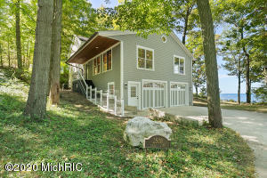 This Lake Michigan year-round cottage/home sits on a double lot, well back from the bluff.  Less than a mile north of Big Red lighthouse, this property offers picturesque lake views. In 2007 this 4-bedroom and 2-bath cottage was completely remodeled down to the studs with plaster interior, custom cherry woodwork, and a 30'x30' addition. The home features a spacious two-stall attached garage, and large great room and entryway, which is ideal for entertaining. The large concrete driveway offers ample parking for guests. The stone fireplace with wood burner and Brazilian cherry flooring adds to the charm of this year-round home. The home has a cottage feel with wood shake siding. The spacious lake side deck has been freshly stained, and the exterior has just been professionally painted. Optimal summer sunsets viewed from the outside deck or one of the many westward-facing windows. Enjoy cozy, off-season weekends around the stone fireplace.  In either instance, this home is a perfect year-round retreat in the charming Eagle Crest cottage community.