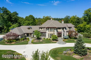 HUGE PRICE REDUCTION! Be sure to check out the VIRTUAL TOUR in the Photos section (or link below).  Gorgeous Wooded estate abounds with nature including deer, turkey, and spectacular birdlife offering privacy by a gated entrance with a long winding ''heated'' driveway back to this refined, finely crafted home designed by Frimodig Design and built by VanderMale Builders.  Meticulously maintained & move-in ready with high levels of finish throughout from cabinets, custom beams, hardware,  custom built-ins, top of the line appliances, to the mechanical systems, interior/exterior lighting, heated garages, 5 (gas and wood) burning fireplaces, whole home generator and the lush landscaping giving the grounds a Frederick Meijer Gardens feel. You will love the open concept throughout with gleaming hardwood floors and 10 to 12' ceilings and many floor to ceiling windows showcasing stunning views of the wooded estate.  The library/office with custom woodworking (walls of bookshelves & fireplace surround) and an attached conference room make working from home a pleasure. Beautiful master suite with soaring windows, fireplace w/ marble surround, loads of custom cabinetry inside the master bath, 2 additional spacious bedrooms upstairs each with private bathroom and walk-in closet and a large bonus room also with private bathroom.  There are two double staircases, one set leading to the upstairs and another set leading to the lower level walkout, this home was well thought out and built to perfection.  You will not want to leave the lower level, with billiard room with separate entertainment area, a second full kitchen with beverage/wine fridge and snack bar just off of the family room with stone fireplace & large patio doors leading to the blue stone patio. Not to mention the lower level includes an additional bedroom with private bath, an in-home gym with a jacuzzi hot tub and plenty of storage space.  The many outdoor living spaces are great for fun and entertaining especially the screened in porch leading to the expansive deck. With too many amenities to include, this estate is truly a must see. Call today for an exclusive tour. Embrace the sights, sounds and rhythms of nature throughout the year in your private oasis.**adjacent 3.85 parcel available for buffer or additional building upon offered for  $250,000.00