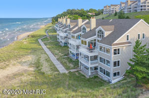 Wow! Here it is! Michigan Beach Life Never Looked So Good! This amazing 3 Bedroom/3 Bath Beach Level Spyglass Condominium is just steps from Lake Michigan!  Professionally remodeled in 2019, this Nautical Nest has a refreshing yet laid back coastal feel throughout! Newly painted, carpeted, decorated, new appliances, and remote Hunter-Douglas blinds. Step out onto the upstairs patio, inhale, listen, and take in the sights, sounds, and breeze of Lake Michigan.  You will be stunned by the incredible experience and panoramic views of Lake Michigan and the Holland Lighthouse, especially from this private end unit.  Or, wander out from the entirely renovated lower level family entertainment/bunkroom area onto the beach level patio with direct access to Lake Michigan Over 1,000 feet of low bluff association beach frontage.  Need a little more fun, check out the Association tennis/pickleball/basketball courts, heated in-ground swimming pool, children's play area or wander off the site onto the State Park Trail System. It's all here, ready for you to start making your own memories and enjoying all that the Spyglass Beach Community has to offer!  Come see it for yourself!
