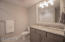 The lower level bath features a granite top, linen closet and tub/shower. Frame mirror is upgrade feature.