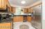 Upgraded kitchen with stainless appliances and custom ceramic tile floors.