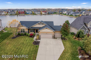 New listing in Hudsonville schools! This three stall walk out ranch is on Cory lake and has outstanding views. The main floor features three bedrooms and two full bathrooms, with the master bedroom having it's own bathroom and attached walk-in closet. The kitchen is very generous in size with a center island and a must needed pantry. The lower level is freshly completed and includes a wet bar, built-in cabinets for the entertainment center, tiled tub/shower and a fourth bedroom. Enjoy outdoor entertaining with your oversized maintenance free deck and your gorgeous stained cement patio area that leads to the lower level. There is also a swim deck in the backyard overlooking Cory lake and the sale includes docking and a paddle boat. Call today for your private showing.