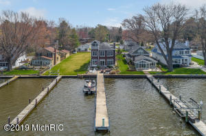 On the shores of Lake Macatawa sits this custom home, perfectly positioned to take in those famous West Michigan sunsets and expansive water views. Close to Holland's channel, this street is one of the area's best kept secrets offering a private feel while still close to Lake Michigan and Holland's bustling downtown. Wonderfully appointed and with elegant coastal charm, the inspired 4 bedroom home is perfect for entertaining both inside and out. Open concept main floor with gourmet kitchen, upgraded appliances, secret wine cellar, dining room, spectacular Mahogany fireplace, and doors to the hardscaped lakeside patio, ideal for taking in the setting and an evening beverage.