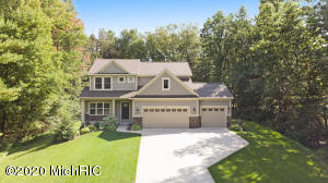 Immaculate custom-built home featuring 5 bedrooms PLUS office shows better than new. Surrounded by nature and unparalleled season-changing views, your nearly 3/4 of an acre private wooded lot can be enjoyed year-round. Built in 2016, this open and airy floor plan boasts almost 3,000 square feet. Kitchen includes quartz countertops with center island, gorgeous tiled backsplash, desirable stainless range hood as well as stainless appliances. Living area features beautifully tiled fireplace, custom built-ins and ample storage.  Upstairs you will enjoy 4 bedrooms and 2 full bathrooms. The large master suite includes double vanities plus double walk-in closets. Finished basement features living/rec room complete with dry bar with quartz countertops. The 5th bedroom and 3rd full bathroom including tiled shower complete this floor.Quality craftsmanship, gorgeous lighting and fixtures throughout. 3 stall garage. Mudroom with lockers. Custom window coverings. Professional landscaping and underground sprinkling. Minutes from downtown Rockford and 20 minutes to downtown Grand Rapids. Rockford Public Schools. Welcome Home!