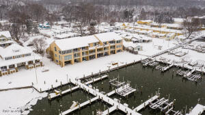 RARE WATERFRONT condo on Lake Macatawa, offered by original owner! Small 9 unit condo development, located on the north shore, overlooking Lake Mac just a half mile from Lake Michigan. Complete with your own 15' x 30' private BOAT SLIP - just seconds away from cruising through the channel past Holland State Park into Lake Michigan, or bobbing in the bays of Macatawa. And just steps away from the Black Lake boardwalk & the well known, charming General Store. Best location in the building, top SW corner w/ amazing southern exposure that can be enjoyed from the extra large deck and thru the wall of windows in the 4 season room.  This condo features a private elevator EXCLUSIVE to this unit ONLY, 4 exterior storage closets, & an extra deep 2-stall garage w/ heat. Comfortable 1800sq. ft layout