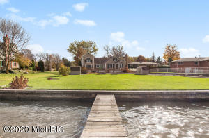 Beautiful Lake Macatawa waterfront!  Nearly 100' of steel and concrete seawall & 100' of permanent dock, 3 deep water boat slips w/ 220/110 electric. Empty lot next door is city property & cannot be built on. This 4+ bedroom home has a 2-story master suite with soaring windows and a loft living area - plenty of space for solitude & reflection. Huge windows throughout allow amazing lake & sunset views from almost every room. Large dining room for entertaining with built-in wine bar. Kitchen w/ custom built solid oak cabinetry, solid surface countertops & high-end appliances. The warm & relaxing den with gas fireplace has amazing views of the expansive level lawn to the lake. Deck with ample lounging space runs the entire lakeside of the home. Underground sprinklers fed by own well. This home has had tons of updates and features added in recent years including a basement remodel, new HVAC, H2O heater, PEX water piping, added insulation, new roof and flooring, 220 line in garage for an electric car.  Generac whole-house generator and Marquis 6-8 person hot tub included in listing. This home is PEARL Energy Efficient Silver Certified!  Fiber optic cable is prepaid through June 2022 for buyer. ONE YEAR HOME WARRANTY VIP PACKAGE INCLUDED.