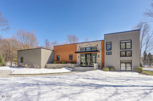 This one of a kind Modern Retreat is located close to beaches, bike paths, and parks on the north side of Holland.  Every detail has been well thought out to provide unmatched character and beauty.  Floor to ceiling windows as you enter provides remarkable views from the entry to the family room all the way out to the custom pool.  The kitchen and pantry have custom Plato touch-latch cabinets, gorgeous Cambria quartz, and a beautiful view of the private lot.  The family room features a curved wall to showcase something special like a baby grand piano.  Upstairs is the Owners Suite, closet and full bathroom as well as an office/library space.  In the lower level you'll find a ''secret'' media room, and a den that can be turned back into bedrooms if needed.  Much more to see than listed here