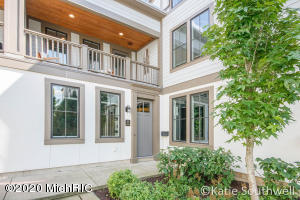 Luxury, location, and convenience in the heart of Gaslight Village. Distinctive light-filled 1,800 SF corner unit condo masterpiece with 2 bedrooms, 2.5 baths, open living spaces, and a spacious balcony overlooking a lush manicured courtyard. You'll find elegance, attention to detail, and upgraded finishes throughout including beautiful stone and hardwood floors, top of the line kitchen with center island and walk-in pantry, and lavish owner's suite complete with large spa bath and two custom-fitted walk-in closets. A rare opportunity to own and experience a turn-key lifestyle right around the corner from the grocery store, restaurants, shopping, award-winning schools, and Reeds Lake. 2 stall heated attached garage with additional guest parking just steps away.