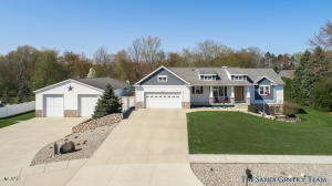Don't Miss this Spectacular Custom Designed and Built Walkout Ranch Home on a Private Wood Acre site beautifully landscaped with a small creek,  play area and fire pit.  Open Kitchen features Quartz Countertops, center island with snack bar, walk in pantry and is fully Applianced. Great room features cathedral ceilings, Gas fireplace, adjoining dining area with Glass Slider to the Entertaining size deck. Master bedroom suite features a large walk in closet, double vanity, and gorgeous granite shower. Finished Lower level family room includes a fireplace & wet bar! Other features include solid doors throughout, main floor laundry, additional composite deck surrounding the pool. Garage is heated, insulated and has stairs down to the lower level. Huge 40x60 Accessory Building  Heated and Insulated with 14' Doors.  This home is a MUST SEE! Underground Sprinkling has a Well. Call today for your private showing!