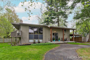Mid-Century Mod home on 1.5 lot of land, miles away from Grand Rapids. 5 bed/ 2 bath with a park-like setting. Many recent updates make this a home you don't want to miss! Located in Grandville schools and fully remodeled down to studs in 2017. Newer appliances and some recent updates include furnace and water heater (2020) and added exterior lighting and outlets. Cozy up by the fireplace which divides the dining and living room on the main floor, serving as a great centerpiece for entertaining. Relax out on the second level deck enjoying all nature has to offer while overlooking the golf course and meadows. The private fenced-in back yard is also great for children, pets, and entertaining with friends.
