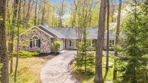 High-quality custom-built home on a quiet park-like site in a premier Thornapple River community. The private wooded site is simply amazing with a babbling stream meandering through it. The custom home was designed and built for the current owner and features large scale rooms, oversized casement windows for tons of natural light, custom-quality woodwork and cabinetry, and 6-panel doors. Features huge open kitchen/dining area, spacious family room with custom masonry fireplace and vaulted ceiling, estate-sized master suite with huge spa bath, walk-in closet plus laundry, charming den/office plus a light-filled sunroom - all with beautiful natural views. Currently used as a one bedroom but adjacent rooms could be converted to bedrooms with a little creativity. Huge open unfinished basement is also the perfect opportunity for expansion. Great investment opportunity given the amazing site, quality and scale of the house, and premium location adjacent.