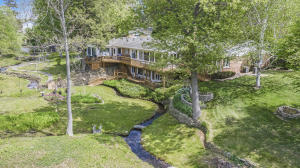 Rare opportunity to own this private 3.4 acre sanctuary with 300' of frontage on All Sports Ackley Lake