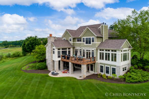 """Stunning detail, quality, and craftsmanship. Designed by Wayne Visbeen, this custom built, one of a kind home features hand carved casings, moldings and beams, a handmade front door, and incredible panoramic views of Ada Valley. The woodwork, design and attention to detail are reminiscent of 100 year old homes in East Grand Rapids. Expansive main floor is open, welcoming and ideal for entertaining. Gourmet kitchen features 2 sub-zero refrigerators, Wolf range, double Wolf ovens, granite countertops, butler pantry as well as access to courtyard bistro and 3-season room. 3-season room offers a masonry fireplace and extraordinary views and sunsets. A grand, 2-way fireplace divides the living room from the light-filled sunroom. Informal dining with hand carved ceiling beams opens to kitchen and living room. Substantial formal dining room perfect for special occasions. Office with leaded glass cabinet doors. Locker room accesses 3 stall garage. Luxurious primary suite with 2 walk-in closets, 2 vanities, soaking tub, and walk-in shower. 2nd floor laundry room with newer washer and dryer and plenty of storage. Lower level includes a wet bar with sub-zero wine cooler, 12"""" crown moldings, tiered home theater room, 2 more bedrooms or home office/gym space with ensuite bathrooms, and walkout to covered patio. New composite deck and railing plus gutter system to keep lower patio dry. Reverse osmosis water, 2 furnaces and 2 AC units. New whole house Generac generator. In 2017 exterior painted with 2 coats. 2.38 acres on cul-de-sac. Community gazebo, picnic tables and pond. Some furnishings to stay with house. Road assessment $125/quarter. Masks required. Don't miss this opportunity to make this house your home!"""