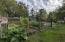 Fenced in garden area with greenhouse and chicken coop