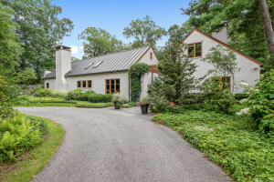 Stunning architectural gem on a private 1.17 acre lot, complete with  bridge for entry. Built in 1962 and impeccably remodeled by Scott Christopher Homes in 2004, this home is one of a kind. The main level boasts the stately original fireplace, reclaimed wood beams and heated slate flooring throughout the chef's kitchen. Floor-to-ceiling windows and french doors open to your outdoor entertaining space and bluestone courtyard. Main-level Master Suite, laundry, formal living room complete with second fireplace plus 2 additional bedrooms. Adjacent is an office with spiral staircase to a loft. Downstairs are 3 additional bedrooms, a vast entertainment space and ample storage. All of this and more; your own private oasis at the end of a cul-de-sac, a short walk from Gaslight Village.