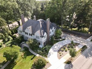 Fall in love with this one-of-a-kind timeless home in beautiful East Grand Rapids. Built in 1928 for J. Stuart Clingman, the famous Widdicomb Furniture Company designer, this historic home features exquisite millwork detailing all hand-carved from zebrawood, maple, and walnut burl. Dramatic arches, leaded glass windows, and five glowing fireplaces are just a few of the elements that provide a grand and enchanting feeling. An entertainer's dream also ideal for family living and equipped with a recently remodeled contemporary double kitchen offering an eat-in island, custom cabinetry and lighting, and a suite of high-end appliances. The formal living room and light-filled sunroom have double doors leading to the oversized deck with views of the expansive yard. A stately dining room, corner den/library, and two powder rooms complete the main floor. Upstairs you'll find five large bedrooms including a spacious master suite and four full bathrooms all updated in 2020-2021. Adjoining the master suite is a bedroom/office with dual walk-in closets and a 2nd-floor laundry room. Additionally, there is a third-story bonus rec room/office and attic storage access. The lower level features a disco/workout room that can double as a speakeasy/poker room if desired or a friendly playroom with coffee bar; a completely remodeled wet bar with wine and beverage fridge, refrigerated wine cellar, office, full bath and storage space. Prime location among historic Plymouth Road estates, 801 Plymouth is the essence of East Grand Rapids living with modern charm and luxury living on a landscaped corner lot only a short stroll from Gaslight Village. Truly a once-in-a-lifetime opportunity to own a stunning example of EGR architectural history.