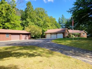 Huge home on beautiful & secluded 1.8 acre lot w/ a bridge outside the fenced backyard that takes you over the stream & into the woods.  Natures paradise!  Home features so much!  5 BR, 3.5 BA, flex room, 3 Season Room w/ access to catwalk & steps to lower patios,  LR, Great Rm, Fam Rm, Rec Rm, 2 wood burning stoves, pretty covered porch, recently painted main level, hardwood floors in the Great Rm, Ceramic tile in DR and Kit, Attic Fan & Replacement Windows throughout. Separate studio apartment where once was 3rd attached stall has private entrance off garage & front of home. 3rd full bath located in studio, extra 2 stall Barn w/ workshop/storage area (potential for 3rd stall). You really just need to see it for yourself! Seller directs Broker to hold all offers until 9/22/2021 at11:00am
