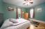 Main floor bedroom with beautiful hardwoods and ceiling fan