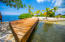 The bridge over the water from the palapa to the white sand beach.