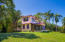 Front view of the home that is surrounded by manicure gardens and lush tropical fruit trees