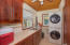 This laundry room has access to a fully bathroom located on the first floor.