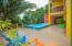 There is a spacious outdoor living space that includes a pool and fenced in yard.