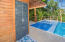 An outdoor shower is located next to the pool for added convenience.